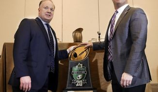 Kentucky head coach Mark Stoops, left, and Northwestern head coach Pat Fitzgerald pose with the trophy during the Music City Bowl coaches' press conference Thursday, Dec. 28, 2017, in Nashville, Tenn. Kentucky and Northwestern are scheduled to play in the game Friday. (AP Photo/Mark Humphrey)