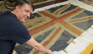 In this Thursday, Dec. 7, 2017, photo, Charles Swift, managing director and curator of the U.S. Naval Academy Museum in Annapolis, Md., looks up from a British flag of the HMS Landrail, which was captured in 1814 by American privateers sailing in the English Channel. It is one of 61 flags recently removed from glass cases at the U.S. Naval Academy for preservation. (AP Photo/Brian Witte)