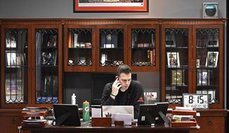 Louisville interim coach David Padgett talks on his cell phone as he starts the day in his office, Friday, Dec. 22, 2017, in Louisville, Ky. The office that formerly belonged to longtime coach Rick Pitino was locked and vacant until his firing in mid-October. Padgett slowly began moving in soon after. (AP Photo/Timothy D. Easley)