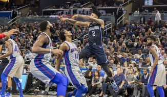 Orlando Magic guard Elfrid Payton (2) passes the ball over Detroit Pistons guard Ish Smith (14) and center Andre Drummond, front left, during the first half of an NBA basketball game in Orlando, Fla., Thursday, Dec. 28, 2017. (AP Photo/Willie J. Allen Jr.)