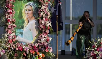 FILE - In this Aug. 11, 2017, file photo, Johanna Morrow plays the didgeridoo during a memorial service for Justine Damond in Minneapolis. Damond was shot and killed by a Minneapolis police Officer Mohamed Noor on July 15, 2017 after she called 911 to report a possible sexual assault near her home. Minnesota Prosecutor Mike Freeman who had promised a decision by year's end, said Thursday, Dec. 28, 2017, he needs more time to decide whether to charge the police officer in the death of Damond. (Aaron Lavinsky/Star Tribune via AP, File)