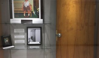 """This Dec. 20, 2017, photo provided by Cambridge Central Schools shows a display case with photos, an illustration and the door that was once on the Principal's office at Cambridge Central Schools in Cambridge, N.Y. Inside the case is the original door from the principal's office that served as the setting for the Normal Rockwell Saturday Evening Post cover in 1953, known as """"Girl With Black Eye,"""" or """"The Shiner."""" Steve Butz, a science teacher at Cambridge High School, preserved the door for display after it was replaced during a renovation project. (Steve Butz/Cambridge Central Schools via AP)"""