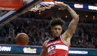 Washington Wizards forward Kelly Oubre Jr. reacts after dunking during the second half of an NBA basketball game against the Houston Rockets, Friday, Dec. 29, 2017, in Washington. The Wizards won 121-103. (AP Photo/Alex Brandon)