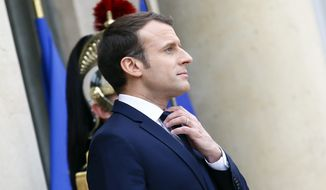 FILE - In this Dec.19, 2017 file photo, French President Emmanuel Macron adjusts his tie at the Elysee Palace, in Paris. As Macron turns 40 Thursday, he's wrapping up a remarkable year. In the seven months since he won a long-shot presidential bid, he has proved to be a key leader in Europe and in the world, at the forefront of the battles against terrorism and climate change and mediating in crises around the Middle East. Now the hard part: transforming France, where critics brand him an arrogant monarch. (AP Photo/Francois Mori, File)