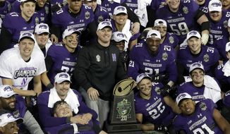 Northwestern head coach Pat Fitzgerald, center, poses with his players after beating Kentucky 24-23 in the Music City Bowl NCAA college football game Friday, Dec. 29, 2017, in Nashville, Tenn. (AP Photo/Mark Humphrey)