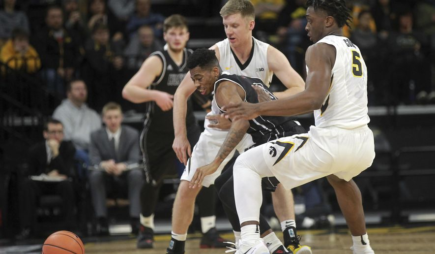 Iowa's Brady Ellingson and Tyler Cook (5) knock the ball away from Northern Illinois' Dante Thorpe during an NCAA college basketball game Friday, Dec. 29, 2017, in Iowa City, Iowa. (David Scrivner/Iowa City Press-Citizen via AP)