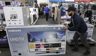 FILE - In this Nov. 23, 2017, file photo, Jesus Reyes pushes a television down an aisle as he shops at a Best Buy store in Overland Park, Kan. Just before the Super Bowl, retailers normally discount their selections of HDTVs and other home-theater essentials making January a good month to shop for electronics. (AP Photo/Charlie Riedel, File)