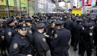 FILE- In this Dec. 31, 2015 file photo, police officers gather at the southern end of Times Square to receive their assignments for New Year's Eve in New York. New York Police Department officials say that while there are no specific or credible threats against the city, they are promising a bigger security detail than ever before at the Sunday, Dec. 31, 2017, New Year's Eve celebration in Times Square. (AP Photo/Seth Wenig)