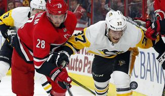 Carolina Hurricanes' Elias Lindholm (28) and Pittsburgh Penguins' Carter Rowney (37) vie for the puck during the second period of an NHL hockey game Friday, Dec. 29, 2017, in Raleigh, N.C. (AP Photo/Karl B DeBlaker)