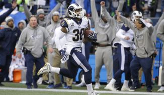 FILE - In this Sunday, Dec. 17, 2017, file photo, Los Angeles Rams running back Todd Gurley runs for his third touchdown in the first half of an NFL football game against the Seattle Seahawks, in Seattle. Gurley realizes he could lose his first NFL rushing title, and maybe even the league MVP award, while he stands on the sidelines at the Coliseum during the regular season finale, Sunday, Dec. 31. (AP Photo/Elaine Thompson, File)