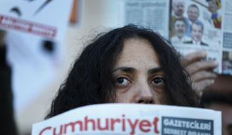 FILE- In this Tuesday, Oct. 31, 2017 file photo, demonstrators hold placards and copies of the Cumhuriyet daily newspaper as they stage a protest outside a court where the trial of about a dozen employees of the newspaper on charges of aiding terror groups, continues in Istanbul. In several countries news organizations are under attack in dramatic ways, as elected governments turn public outlets into their mouthpieces and try to silence critical voices. (AP Photo/Lefteris Pitarakis, File)