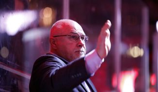 Washington Capitals head coach Barry Trotz waves at the officials before the third period of an NHL hockey game against the New Jersey Devils, Saturday, Dec. 30, 2017, in Washington. The Capitals won 5-2, and with the win, Trotz recorded his 737th career win to become the fifth winningest coach in NHL history. (AP Photo/Alex Brandon)