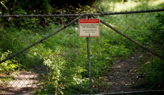 "FILE- In this Wednesday, Aug. 16, 2017 file photo, a ""No trespassing"" sign is displayed at an old tannery waste dump used by Wolverine World Wide in Belmont, Mich. Some private wells in the area have tested positive for elevated levels of per- and polyfluoroalkyl substances called PFAS, also called perfluorinated chemicals, or PFCs. Michigan, where the large city of Flint continues to recover from a lead-tainted water supply, is now racing to combat a new threat to tap water at sites across the state: chemicals long used in firefighting, waterproofing, carpeting and other products. (Neil Blake /The Grand Rapids Press via AP)"
