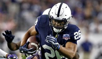 Penn State running back Saquon Barkley (26) carries as Washington linebacker Ben Burr-Kirven reaches for a tackle during the second half of the Fiesta Bowl NCAA college football game Saturday, Dec. 30, 2017, in Glendale, Ariz. (AP Photo/Ross D. Franklin) **FILE**
