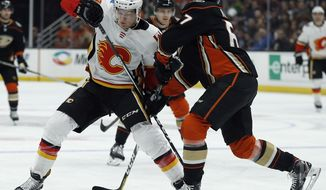 Anaheim Ducks center Rickard Rakell, right, of Sweden, blocks out Calgary Flames center Mark Jankowski (77) from advancing the puck during the first period of an NHL hockey game in Anaheim, Calif., Friday, Dec. 29, 2017. (AP Photo/Alex Gallardo)