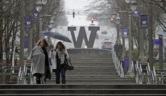 Two pedestrians share an umbrella in the rain, Friday, Dec. 29, 2017, in downtown Tacoma, Wash. A winter storm moving through the Pacific Northwest Friday brought a mixture of showers, mountain snow and freezing rain to the area. (AP Photo/Ted S. Warren)