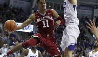 Oklahoma guard Trae Young (11) passes the ball around TCU forward Vladimir Brodziansky (10) during the first half of an NCAA college basketball game, Saturday, Dec. 30, 2017, in Fort Worth, Texas. (AP Photo/Richard W. Rodriguez)