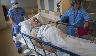 In a Thursday, Dec. 14, 2017 photo, Herb Ball of Cottage Grove, Ore. is wheeled into the operating room at Sacred Heart Medical Center at Riverbend in Springfield, Ore.  for a transcatheter aortic valve replacement (TAVR), a minimally invasive alternative to open heart surgery. (Brian Davies/The Register-Guard via AP)