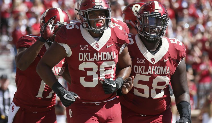 In this Oct. 7, 2017, photo, Oklahoma fullback Dimitri Flowers (36) celebrates a touchdown with teammate Erick Wren (58) during an NCAA college football game against Iowa State in Norman, Okla. No. 2 Oklahoma and No. 3 Georgia meet for the first time Monday at the Rose Bowl in a College Football Playoff semifinal that features two very different ways of playing offense. (AP Photo/Sue Ogrocki)