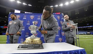 Clemson defensive tackle Jabril Robinson, center, defensive tackle Sterling Johnson, left, safety Alex Dalton get an up close look at the trophy during media day for the upcoming Sugar Bowl semi-final playoff game against Alabama, for the NCAA football national championship, in New Orleans, Saturday, Dec. 30, 2017. (AP Photo/Gerald Herbert)
