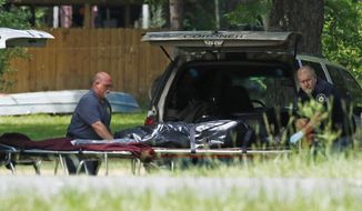 FILE - In this May 28, 2017, file photo, officials remove a body from a Brookhaven, Miss., residence, following a violent overnight shooting rampage that left a sheriff's deputy and seven other people dead at various locations. The scope of the violence against one family and its relations, made it a top Mississippi news story for 2017. (AP Photo/Rogelio V. Solis, File)