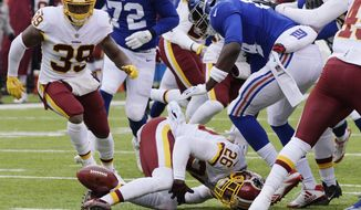 Washington Redskins cornerback Bashaud Breeland (26) loses control of the ball during the first half of an NFL football game against the New York Giants Sunday, Dec. 31, 2017, in East Rutherford, N.J. (AP Photo/Bill Kostroun)