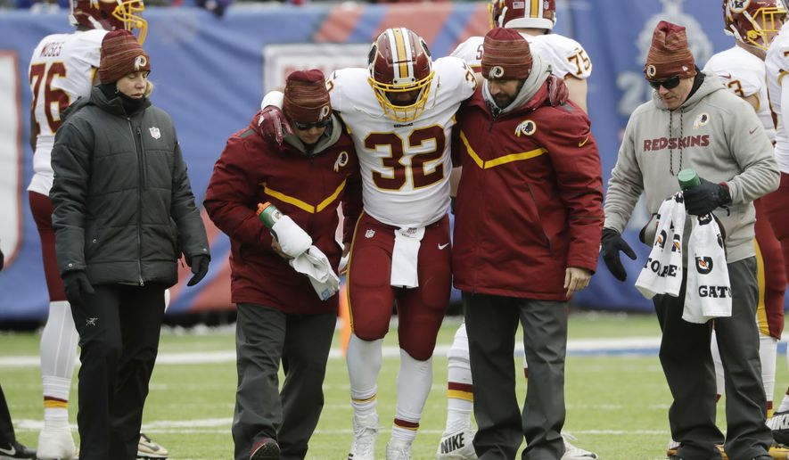 Trainers assist Washington Redskins running back Samaje Perine (32) after he's injured on a play during the first half of an NFL football game against the New York Giants Sunday, Dec. 31, 2017, in East Rutherford, N.J. (AP Photo/Mark Lennihan)