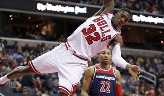 Chicago Bulls guard Kris Dunn (32) hangs from the rim after dunking in front of Washington Wizards forward Otto Porter Jr. (22) during the first half of an NBA basketball game Sunday, Dec. 31, 2017, in Washington. (AP Photo/Alex Brandon)