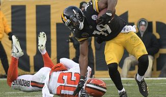 Pittsburgh Steelers wide receiver JuJu Smith-Schuster (19) eludes a tackle by Cleveland Browns strong safety Briean Boddy-Calhoun (20) during the second half of an NFL football game in Pittsburgh, Sunday, Dec. 31, 2017. (AP Photo/Don Wright)