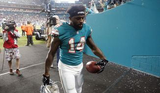 Miami Dolphins wide receiver Jarvis Landry (14) leaves the field after scoring a touchdown and being ejected from the game for unsportsmanlike conduct, during the second half of an NFL football game against the Buffalo Bills, Sunday, Dec. 31, 2017, in Miami Gardens, Fla. (AP Photo/Wilfredo Lee)