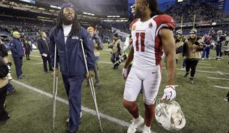 Seattle Seahawks' Richard Sherman, left, greets Arizona Cardinals' Larry Fitzgerald after an NFL football game Sunday, Dec. 31, 2017, in Seattle. Arizona won 26-24. (AP Photo/Elaine Thompson)