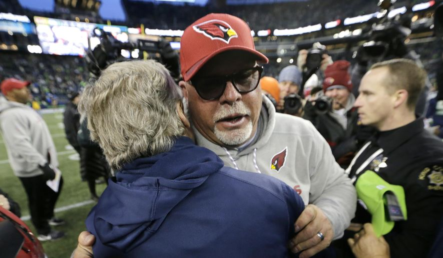 Arizona Cardinals head coach Bruce Arians, front right, hugs Seattle Seahawks head coach Pete Carroll, left, after an NFL football game, Sunday, Dec. 31, 2017, in Seattle. (AP Photo/John Froschauer) **FILE**