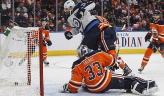 Winnipeg Jets' Blake Wheeler (26) watches the puck cross the line as Edmonton Oilers goalie Cam Talbot (33) tries to make the save during the first period of an NHL hockey game Sunday, Dec. 31, 2017, in Edmonton, Alberta. (Jason Franson/The Canadian Press via AP)
