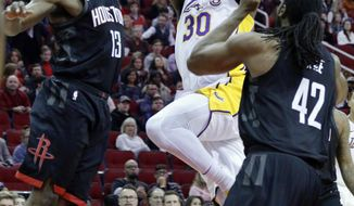 Los Angeles Lakers forward Julius Randle (30) shoots between Houston Rockets guard James Harden (13) and center Nene (42) during the first half of an NBA basketball game Sunday, Dec. 31, 2017, in Houston. (AP Photo/Michael Wyke)