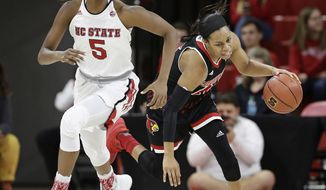North Carolina State's Chelsea Nelson (5) and Louisville's Asia Durr chase the ball during the first half of an NCAA college basketball game in Raleigh, N.C., Sunday, Dec. 31, 2017. (AP Photo/Gerry Broome)