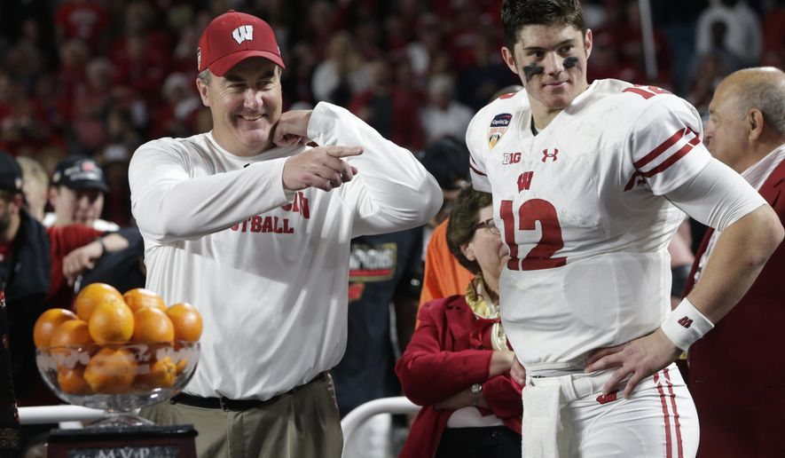 Wisconsin head coach Paul Chryst and quarterback Alex Hornibrook (12) stand next to the MVP trophy at the end of the Orange Bowl NCAA college football game against Miami, Saturday, Dec. 30, 2017, in Miami Gardens, Fla. Hornibrook won the MVP trophy. Wisconsin defeated Miami 34-24. (AP Photo/Lynne Sladky)