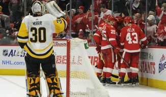 Pittsburgh Penguins goaltender Matt Murray (30) drinks as Detroit Red Wings congratulate center Frans Nielsen (51), of Denmark, after he scored a goal during the second period of an NHL hockey game in Detroit, Sunday, Dec. 31, 2017. (AP Photo/Jose Juarez)