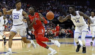 St. John's guard Bashir Ahmed (1) has the ball knocked away by Seton Hall forward Ismael Sanogo (14) in front of Seton Hall forward Desi Rodriguez (20) during the first half of an NCAA college basketball game, Sunday, Dec. 31, 2017, in Newark, N.J. (AP Photo/Adam Hunger)