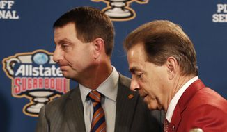 Clemson head coach Dabo Swinney and Alabama head coach Nick Saban, left, greet each other at a joint news conference with the Sugar Bowl trophy for their upcoming semi-final playoff game, for the NCAA football national championship, in New Orleans, Sunday, Dec. 31, 2017. (AP Photo/Gerald Herbert)