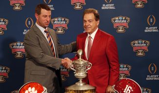 Clemson head coach Dabo Swinney and Alabama head coach Nick Saban, left, pose with the Sugar Bowl trophy for their upcoming semi-final playoff game, for the NCAA football national championship, in New Orleans, Sunday, Dec. 31, 2017. (AP Photo/Gerald Herbert)