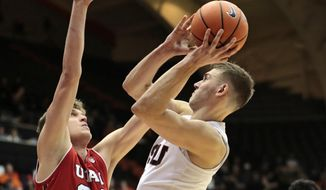 Oregon State's Tres Tinkle, right, tries to shoot while guarded by Utah's Jayce Johnson, left in the first half of an NCAA college basketball game in Corvallis, Ore., Sunday, Dec. 31, 2017. (AP Photo/Timothy J. Gonzalez)