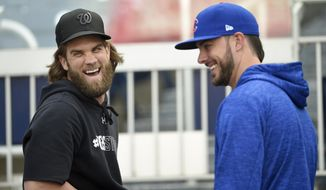 FILE - In this Oct. 5, 2017, file photo, Washington Nationals' Bryce Harper, left, laughs with Chicago Cubs' Kris Bryant at Nationals Park in Washington, the day before Game 1 of a National League Division Series. Harper and Bryant are expected to continue their star performances in 2018. (AP Photo/Nick Wass, File)