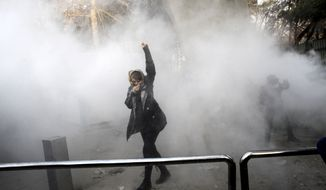 In this Saturday, Dec. 30, 2017, photo taken by an individual not employed by The Associated Press and obtained by the AP outside Iran, a university student attends a protest inside Tehran University while a smoke grenade is thrown by anti-riot Iranian police, in Tehran, Iran. (AP Photo, File)