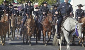Los Angeles Police Chief Charlie Beck leads on a white horse with fellow police officers during the 129th Rose Parade in Pasadena, Calif., Monday, Jan. 1, 2018. (Walt Mancini/Los Angeles Daily News via AP)