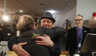 Steve DeAngelo, CEO , center, and brother Andrew DeAngelo, chief revenue officer, right, make the first sale of recreational marijuana to Henry Wykowski at Harborside marijuana dispensary, Monday, Jan. 1, 2018, in Oakland, Calif. Starting New Year's Day, recreational marijuana can be sold legally in California. (AP Photo/Mathew Sumner)