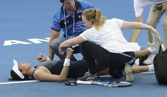Garbine Muguruza of Spain is treated by medical staff after she suffered cramps in her match against Aleksandra Krunic of Serbia during the Brisbane International tennis tournament in Brisbane, Australia, Tuesday, Jan. 2, 2018. Muguruza fell to the court behind the baseline in the third set before retiring from her opening match. (AP Photo/Tertius Pickard)