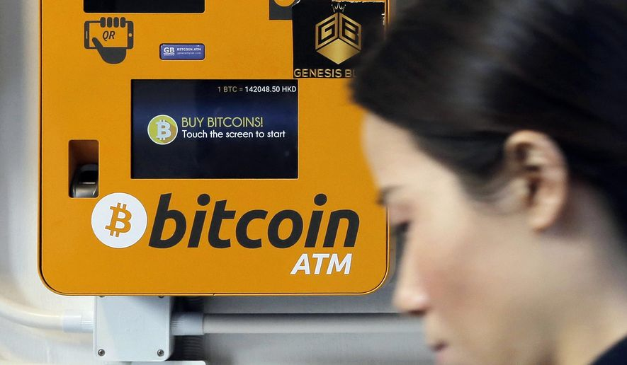 In this Dec. 21, 2017 file photo, a woman walks past the Bitcoin ATM in Hong Kong. (AP Photo/Kin Cheung, File) **FILE**