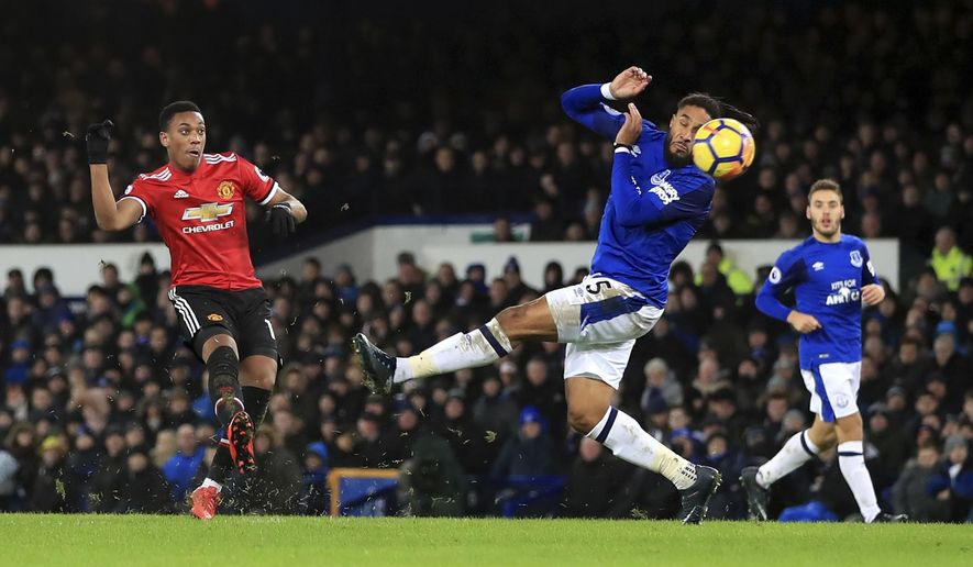 Manchester United's Anthony Martial, left, scores his side's first goal of the game, during the English Premier League soccer match between Everton and Manchester United, at Goodison Park, in Liverpool, England, Monday, Jan. 1, 2018. (Peter Byrne/PA via AP)