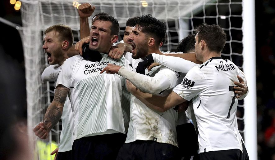 Liverpool's Ragnar Klavan, left, celebrates scoring his side's first goal of the game against Burnley with team-mates including Liverpool's Dejan Lovren, second left, during the English Premier League soccer match against Burnley at Turf Moor, Burnley, England, Monday Jan. 1, 2018. (Martin Rickett/PA via AP)