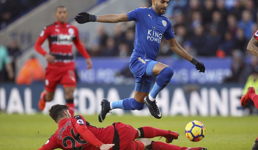 Leicester City's Riyad Mahrez, right, and Huddersfield Town's Christopher Schindler battle for the ball during their English Premier League soccer match at the King Power Stadium in Leicester, England, Monday Jan. 1, 2018. (Nigel French/PA via AP)